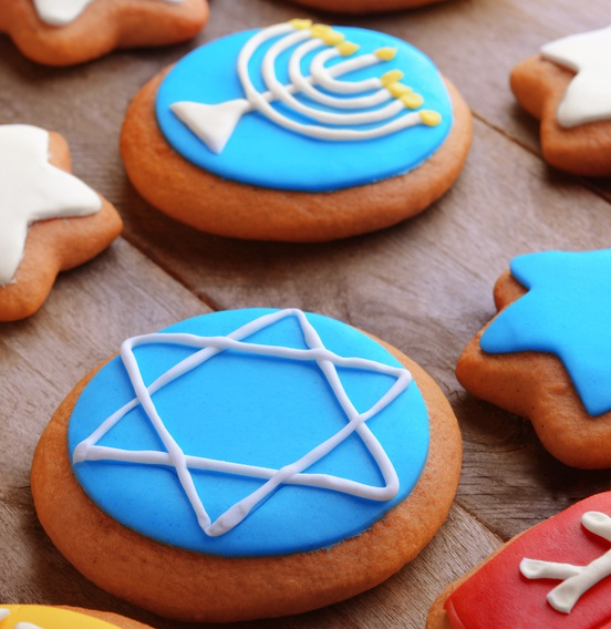 Tasty glazed cookies for Hanukkah on wooden table, closeup